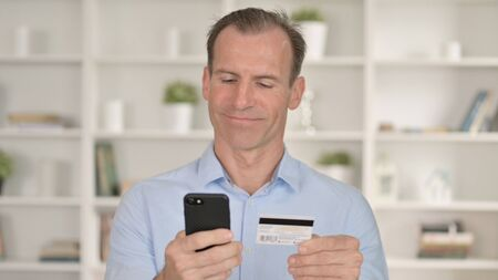 Portrait of Middle Aged Businessman making Successful Payment on Smartphone 免版税图像 - 148658396
