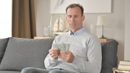 Serious Middle Aged Businessman Counting Dollar at Home