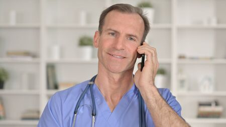 Portrait of Cheerful Middle Aged Doctor Talking on Smartphone 免版税图像