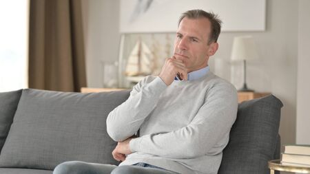 Serious Middle Aged Businessman Sitting on Sofa and Thinking