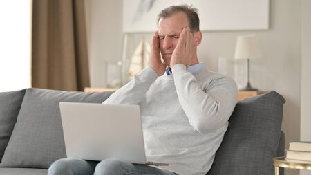 Hardworking Middle Aged Businessman having Headache on Sofa