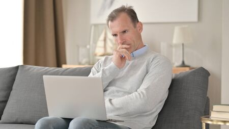 Middle Aged Businessman Thinking and working on Laptop on Sofa 免版税图像