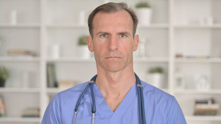 Portrait of Serious Middle Aged Doctor looking at Camera 免版税图像