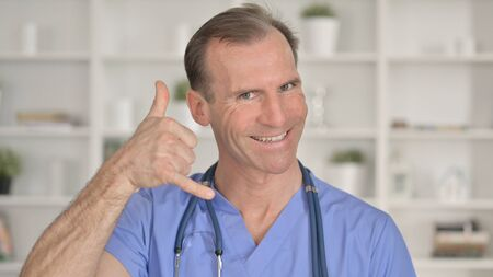Portrait of Middle Aged Doctor showing Call me for Help Sign