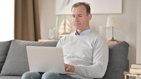 Professional Middle Aged Businessman using Laptop on Sofa 免版税图像