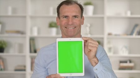 Smiling Middle Age Businessman holding Tablet with Chroma Key Screen 免版税图像