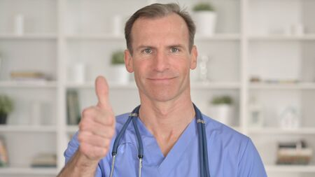 Portrait of Successful Middle Aged Doctor showing Thumbs Up 免版税图像 - 148658416