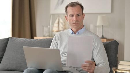 Middle Aged Businessman doing Paperwork with Laptop on Sofa