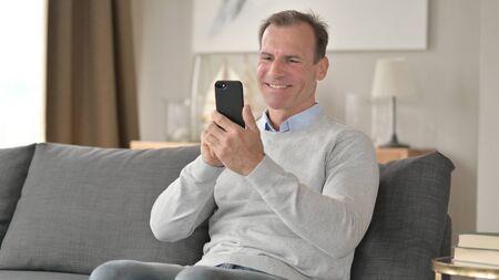Middle Aged Businessman Celebrating Success on Smartphone on Sofa