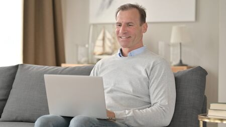 Middle Aged Businessman Talking during Video Chat on Laptop