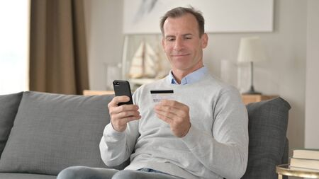 Excited Middle Aged Man making Successful Payment on Smartphone 免版税图像