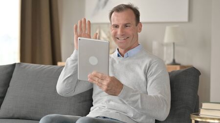 Middle Aged Businessman doing Video Chat on Tablet 免版税图像 - 148658432