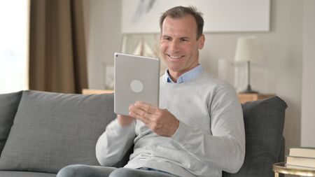 Middle Aged Businessman doing Video Chat on Tablet at Home
