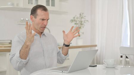 Sad Middle Aged Man having Failure on Laptop at Home