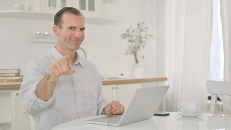 Cheerful Middle Aged Man with Laptop Pointing with Finger