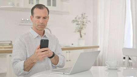 Busy Middle Aged Man Using Smartphone