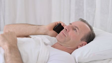 Middle Aged Man Talking on Phone in Bed