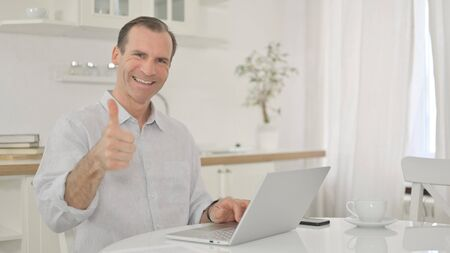 Positive Middle Aged Man with Laptop doing Thumbs Up