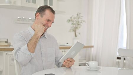 Middle Aged Man Celebrating Success on Tablet at Home Zdjęcie Seryjne