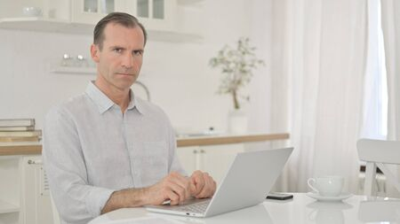 Serious Middle Aged Man with Laptop Looking at the Camera Zdjęcie Seryjne