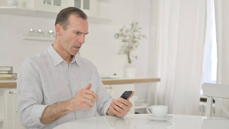 Sad Middle Aged Man having Failure on Smartphone at Home