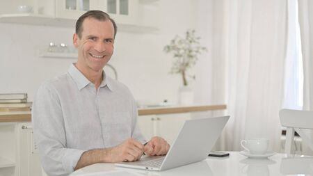 Cheerful Middle Aged Man with Laptop Smiling at the Camera