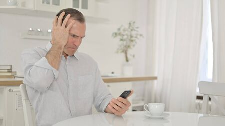 Middle Aged Man Reacting to Loss on Smartphone 免版税图像