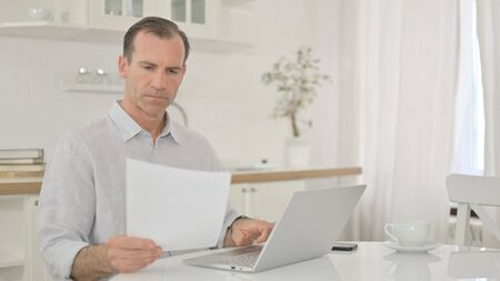Focused Middle Aged Man working on Laptop and Document at Home Stock fotó