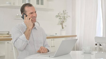 Cheerful Middle Aged Man Talking on Smartphone at Home Stock fotó