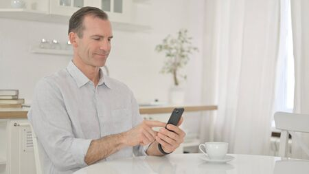 Attractive Middle Aged Man using Smartphone at Home