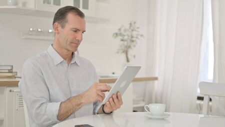 Cheerful Middle Aged Man using Tablet at Home