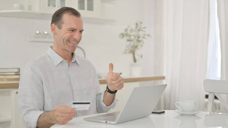 Middle Aged Man making Successful Online Payment via Laptop 免版税图像