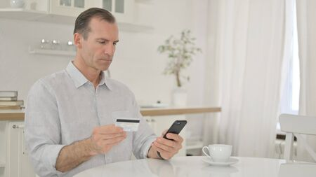Middle Aged Man making Successful Payment on Smartphone