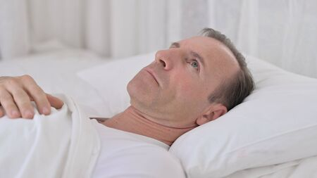 Pensive Middle Aged Man Awake in Bed Thinking