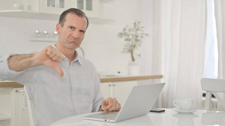 Upset Middle Aged Man with Laptop doing Thumbs Down