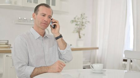 Cheerful Middle Aged Man Talking on Smartphone at Home 免版税图像