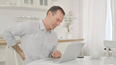 Middle Aged Man with Laptop having Back Pain at Home