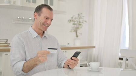 Online Shopping on Smartphone by Happy Middle Aged Man 免版税图像 - 149610058