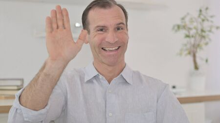 Portrait of Middle Aged Man Waving on Video Call