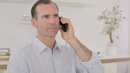 Close Up of Middle Aged Man Talking on Smartphone