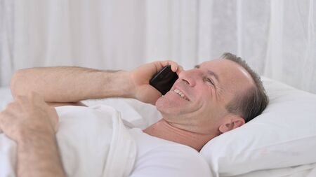 Happy Middle Aged Man Talking on Smartphone in Bed 免版税图像 - 149610147