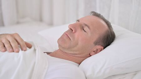 Comfortable Middle Aged Man Sleeping in Bed 免版税图像