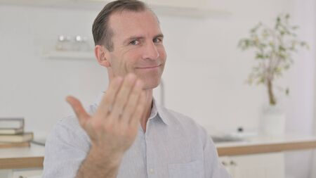 Portrait of Middle Aged Man Pointing Finger and Inviting