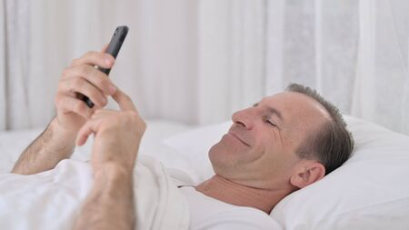 Middle Aged Man using Smartphone in Bed