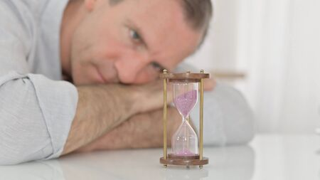 Sad Middle Aged Man Looking at Hourglass in Anticipation at Home 免版税图像 - 149609735