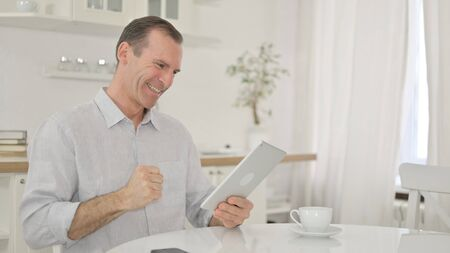 Excited Middle Aged Man having Success on Tablet at Home