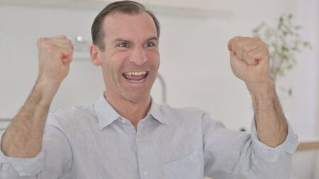 Portrait of Cheerful Middle Aged Man Celebrating Success