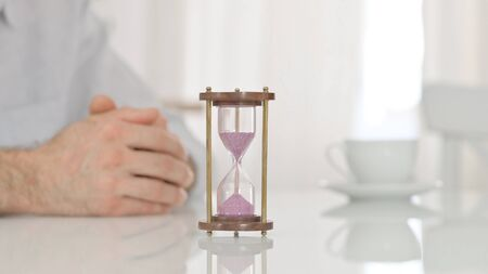 Hourglass on a Table next to Hands of a Man Waiting Impatiently 免版税图像 - 149610234