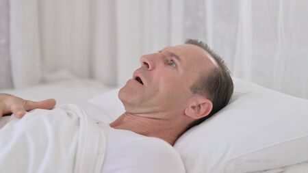 Worried Middle Aged Man having Nightmare in Bed