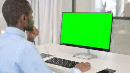 Pensive Businessman Working on Desktop with Green Chroma Key Screen